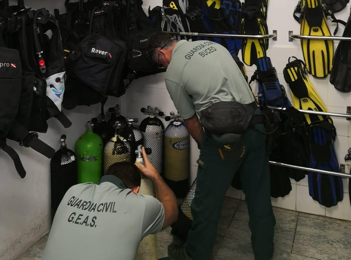 Agentes inspeccionado las botellas.